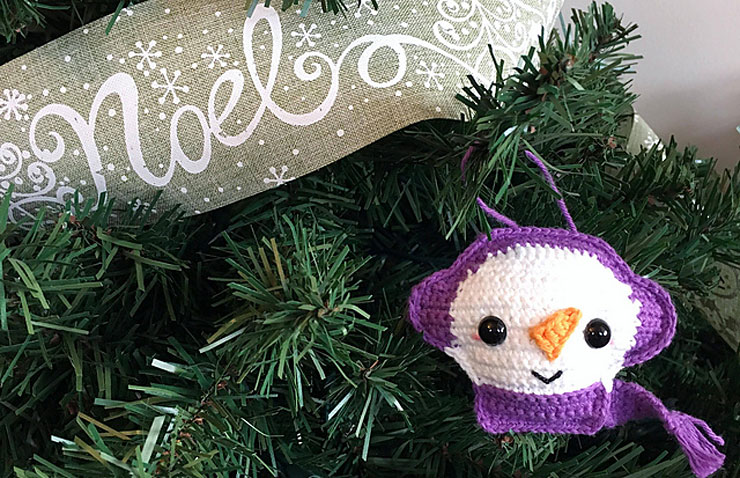 crocheted snowman ornament with purple earmuffs